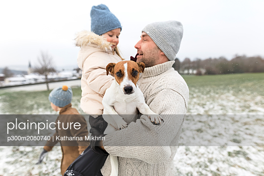 Father with two children and dog in winter landscape - p300m2080740 von Katharina Mikhrin
