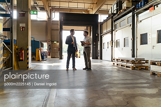 Businessman discussing with colleague while standing at factory - p300m2225145 by Daniel Ingold