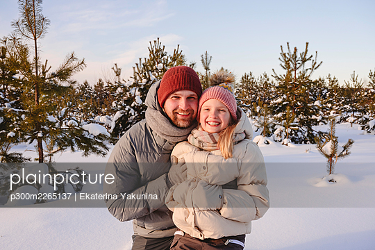 Smiling father and daughter in warm clothing during sunset - p300m2265137 by Ekaterina Yakunina