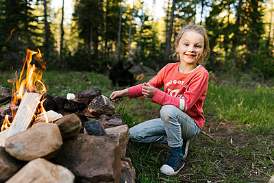 Portrait of smiling girl (6-7) roasting marshmallow above campfire, Wasatch Cache National Forest - p1427m2213551 by Jessica Peterson