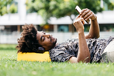 Man lying on a meadow listening music with headphones while using mobile phone, Barcelona, Spain - p300m2131987 by Josep Rovirosa
