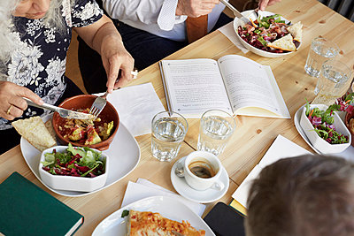 High angle view of friends having food at table in book club - p426m2023007 by Maskot