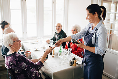 Happy Owner giving credit card to senior adult while sitting by table with friends - p426m2149113 by Maskot