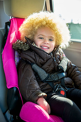 Mixed race girl smiling in back seat of car - p555m1419550 by Inti St Clair photography