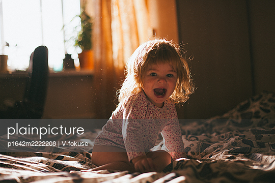 Happy toddler girl sits on bed in the sunshine  - p1642m2222208 by V-fokuse