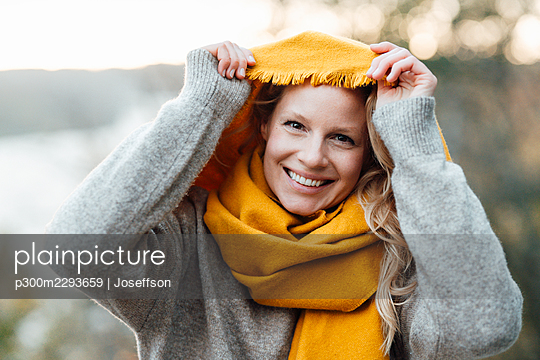 Woman smiling while holding yellow scarf - p300m2293659 by Joseffson