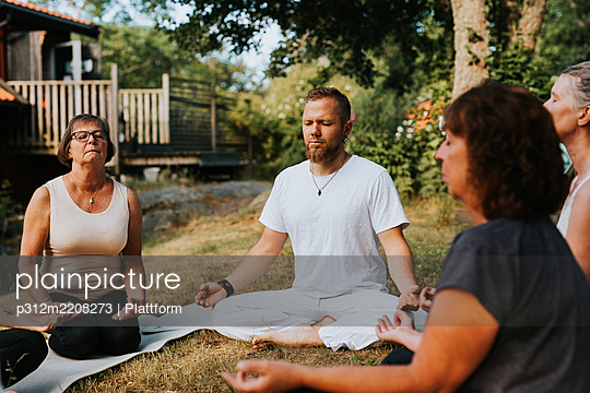 People meditating in garden - p312m2208273 by Plattform