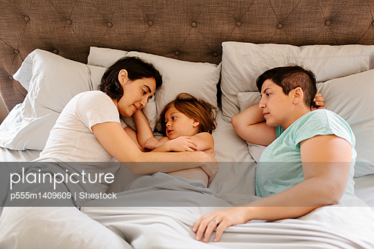Caucasian family laying in bed - p555m1409609 by Shestock