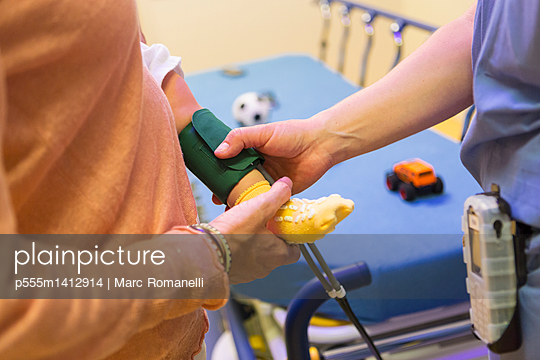 Doctor measuring blood pressure on leg of baby boy - p555m1412914 by Marc Romanelli