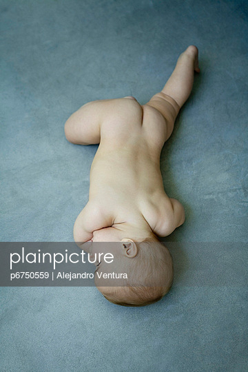 Nude baby lying on stomach on the ground - p6750559 by Alejandro Ventura