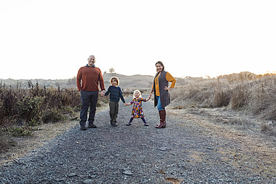 Portrait of Family Holding hand in rural road - p1166m2095125 by Cavan Images