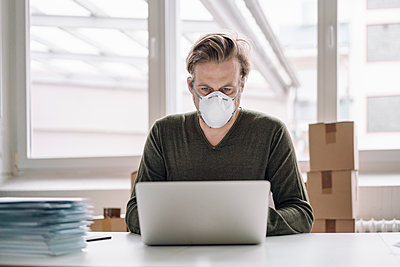 Businessman wearing protective mask and using laptop - p300m2171048 by Joseffson