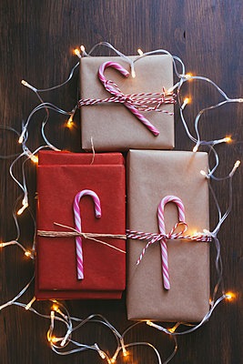Wrapped Christmas presents with decorations and lights on wooden background - p301m2039629 by Alexandra C. Ribeiro