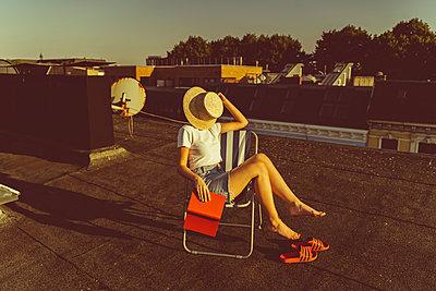 Junge Frau sitzt entspannt mit Buch auf Hausdach - p432m2260305 von mia takahara