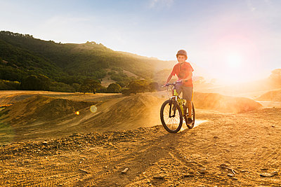Mixed race boy riding dirt bike on track - p555m1304744 by Sollina Images