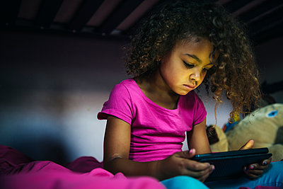 Mixed race girl using digital tablet on bed - p555m1413949 by Inti St Clair photography