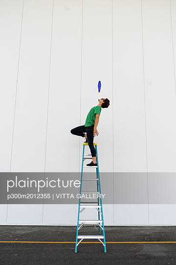 Acrobat standing on ladder, juggling - p300m2012355 von VITTA GALLERY
