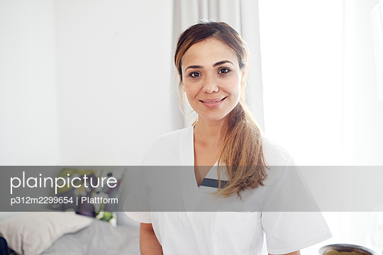 Smiling nurse looking at camera - p312m2299654 by Plattform