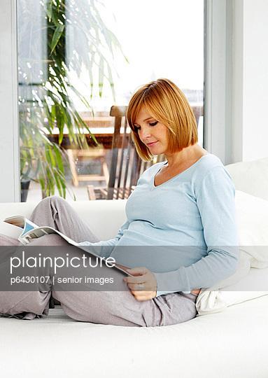 Schwangere Frau liest Zeitschrift  - p6430107 von senior images