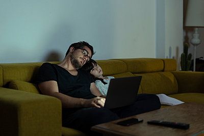 Father with daughter sitting on couch using laptop at night - p300m2069595 von Eloisa Ramos