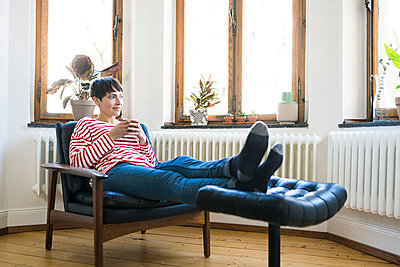 Short-haired woman relaxing in lounge chair holding coffee mug in stylish apartment - p300m2083842 by Steve Brookland