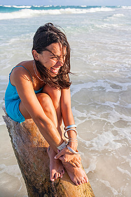 Young woman sitting on log above sea, Tulum, Quintana Roo, Mexico - p429m1547897 by RUSS ROHDE