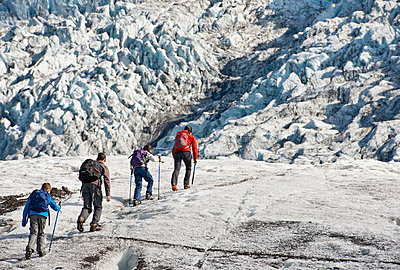 Family walking on glacier - p429m726998f by Henn Photography