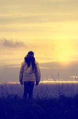 Mädchen betrachtet Sonnenuntergang - p794m945679 von Mohamad Itani