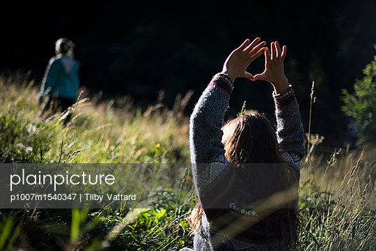 People meditating in the grass of a field at sunrise - p1007m1540347 by Tilby Vattard