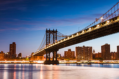 Low angle view of illuminated Manhattan Bridge over East river against blue sky at dusk - p1166m1230524 by Cavan Images