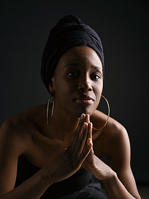 Portrait confident African American woman in headscarf and hoop earrings against black background - p1192m1403553 by Hero Images