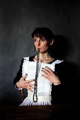 Chambermaid with pearl necklace in mouth, portrait - p1521m2193356 by Charlotte Zobel