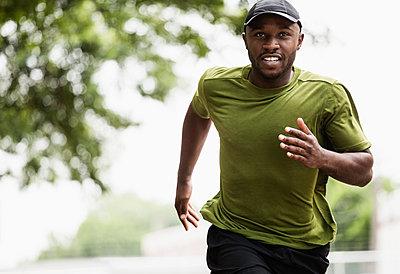 Black man running in park - p555m1420913 by Roberto Westbrook