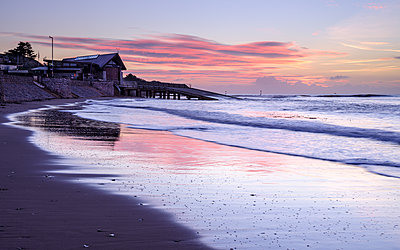 Tranquil dawn with the RNLI Station reflected in the wet beach, Exmouth, Devon, England, United Kingdom - p871m2113982 by Baxter Bradford