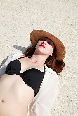 Woman with hat lying on the beach - p1105m2082560 by Virginie Plauchut