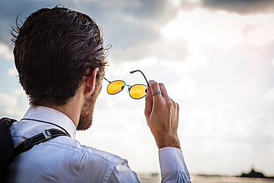 Rear view of businessman with sunglasses looking against sky - p1166m1097154f by Cavan Images