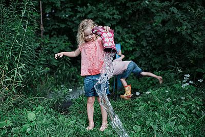 Full length of sister pouring water from rubber boot while brother amidst plants at park - p1166m2024986 by Cavan Images