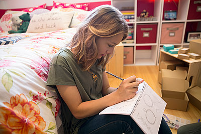 Girl drawing designing jewelry in bedroom - p1192m1158031 by Hero Images