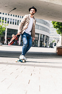Young man with guitar riding skateboard in the city - p300m2004539 by Uwe Umstätter