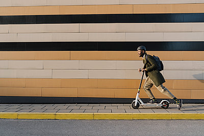 Stylish man with helmet and scooter passing a building - p300m2155248 by Hernandez and Sorokina