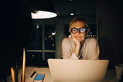Tired mature female professional staring at laptop while sitting with hand on chin working late in office - p426m2194765 by Maskot