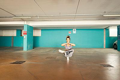 Woman practising yoga in parking lot - p429m2019433 by Ingolf Hatz