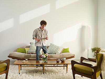 Mixed race man listening to headphones in living room - p555m1411190 by Alberto Guglielmi