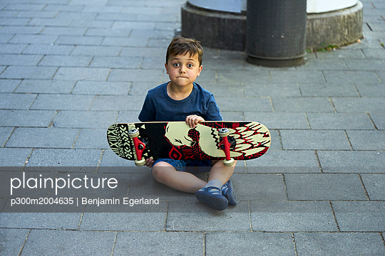 Portrait of astonished little boy sitting on pavement with skateboard - p300m2004635 von Benjamin Egerland