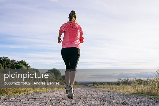 Female runner jogging on country road during sunny day - p300m2273462 by Andrés Benitez