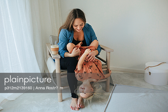 Mother and daughter playing together - p312m2139160 by Anna Rostršm