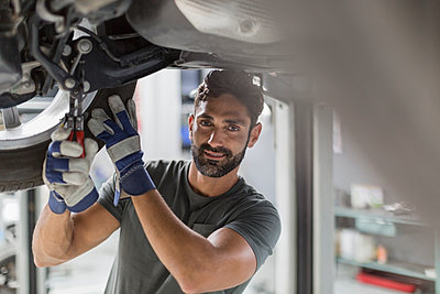 Portrait confident male auto mechanic working under car in auto repair shop - p1023m1542429 by Martin Barraud