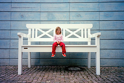 little girl sitting on huge bench - p1053m793693 by Joern Rynio