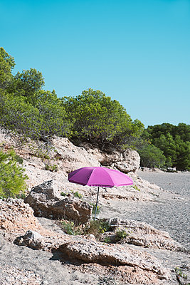 Lonely pink parasol on the beach next to a rock formation - p1423m2215056 by JUAN MOYANO