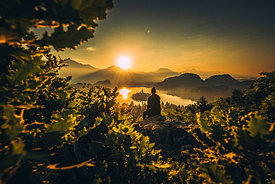 Person watching an early morning sunrise at Lake Bled - p1455m2043699 by Ingmar Wein